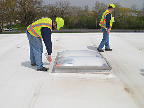 two roofers wearing hard hats inspecting membrane roof