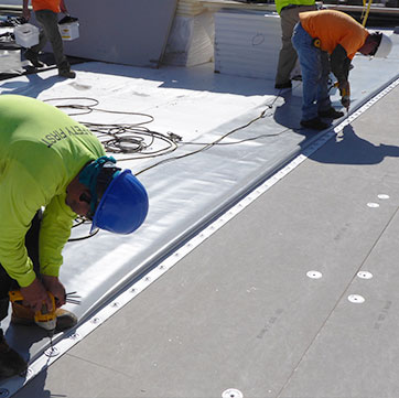 two roofers replacing a roof