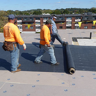 Three roofers installing EPDM roof