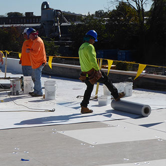 Three roofers wearing hard hats installing TPO roof